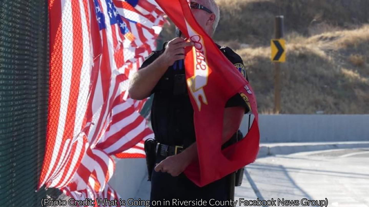 Officer takes down ruined memorial flags